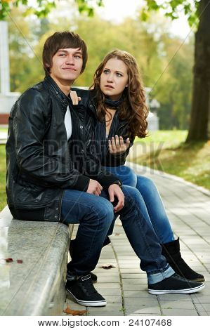 conflict and stress in young people couple relationship outdoors. Grining man and sad girl