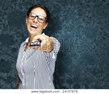 portrait of middle aged woman using tv control against a vintage wall