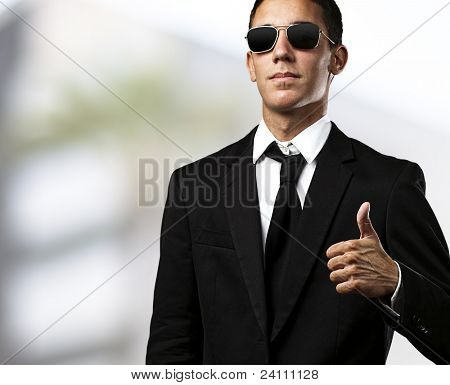portrait of young man in suit with sunglasses and thumbs up with a city as a background
