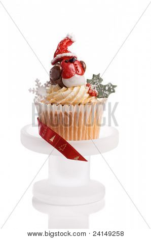 Christmas robin redbreast made from fondant icing on top of festive cupcake with white background