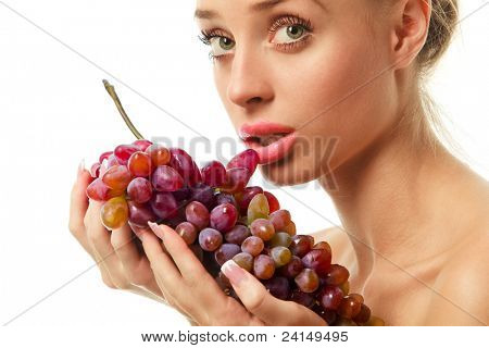 Beautiful young woman holding a bunch of red grapes