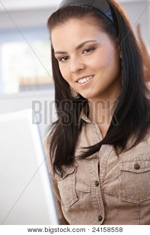 Young female browsing internet on laptop at home, smiling.?