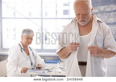 Mature male patient undressing at doctor's room.?