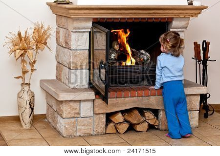 Small girl warms by the fireplace