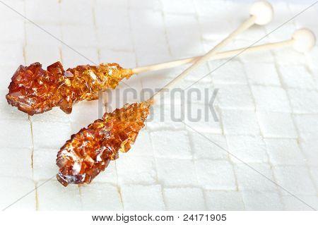 candy brown sugar on a stick lies on white lumpy sugar