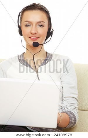 Portrait of young woman wearing headset and using laptop while sitting on couch isolated