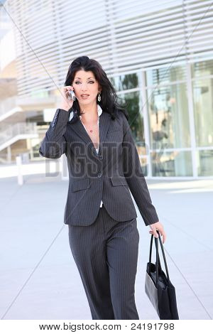 A pretty business woman on the phone at office building