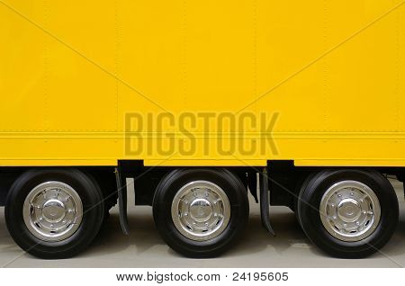 Detail of the empty yellow side of a large truck with three wheels
