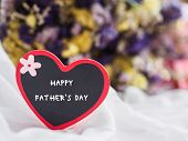 Happy Fathers Day Concept. Wooden Tag With Happy Fathers Day Text And Two Red Heart On Dry Flower  poster
