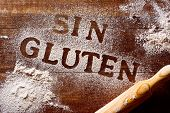 high-angle shot of a wooden table sprinkled with a gluten free flour where you can read the text sin poster
