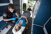 stock photo of triage  - Emergency medical professionals  caring for senior patient - JPG