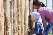 Children Are Looking Through The Hole In The Fence. The Manifestation Of Curiosity poster