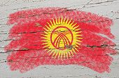 Flag Of Kyrghyzstan On Grunge Wooden Texture Painted With Chalk