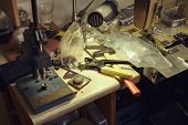 Picture Of A Tailors Desktop With Tools And Rivet Press. poster