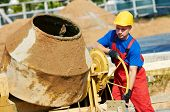 foto of millwright  - builder laborer man working with front of concrete cement mixer at construction site - JPG