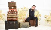 Macho Elegant On Strict Face Sits Tired Near Pile Of Vintage Suitcase. Man, Butler With Beard And Mu poster
