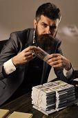 Elegant Man In Suit. Man Sitting At Table With Piles Of Money, Counting Profit. Illegal Cash Concept poster