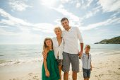 Beautiful Happy Family On Vacation Embracing In Front Of Ocean poster