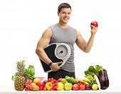 Young man in sportswear holding a weight scale and an apple behind a table with fruit and vegetables poster