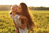 Happy Enjoying Mother Hugging Her Laughing Kid Girl On Sunset Bright Summer Background. Closeup Port poster
