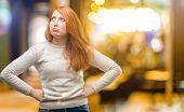 Beautiful young redhead woman doubt expression, confuse and wonder concept, uncertain future at nigh poster