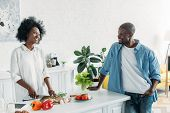 African American Man Looking At Wife Cooking Breakfast In Kitchen At Home poster