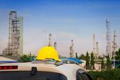 Helmet On The Roof Of Car,oil Refinery Plant,oil Tank And Oil Storage At Sunset.thai Oil Refinery In poster