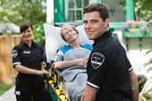 picture of stretcher  - Male ambulance professional with happy senior woman on stretcher - JPG