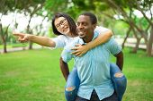 Happy Young Man Giving Piggyback Ride To Girlfriend Or Friend. Asian Woman Wearing Glasses Giving Di poster