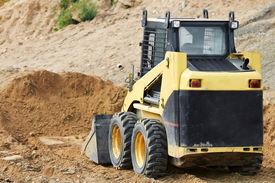 pic of skid-steer  - skid steer loader moving sand soil at construction area outdoors - JPG