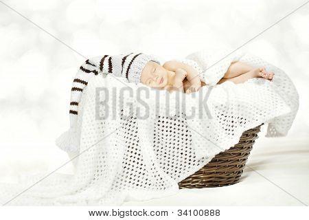 Sleeping Newborn Baby In Woolen Hat Lying In Basket With Blanket