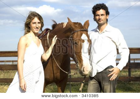 Young Couple Posing With Their Horse