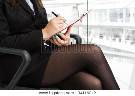 Businesswoman taking notes while sitting on a chair