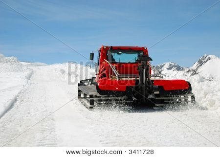 Red Catterpillar Tractor On Snow Slope Against Blue Sky