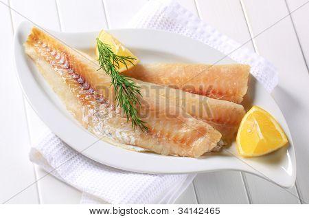 frisches Fischfilet auf einem weißen China-Teller mit Zitronenspalten