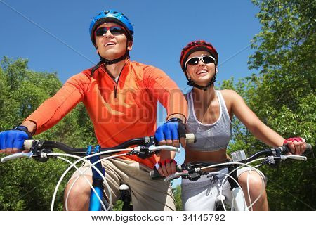 Young smiling couple cycling through summer park