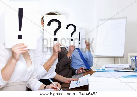 Businessmen in office with question marks