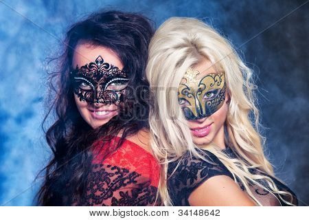 Portrait happy young girls under masks on the party