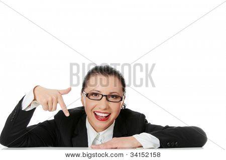 Smiling businesswoman wearing black suit is sitting and pointing at down. Isolated on the white background.