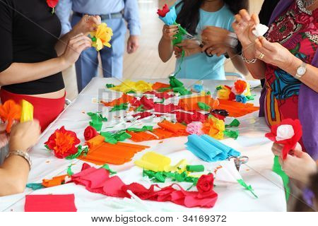 Hands of people standing near table make artificial flowers of tissue paper