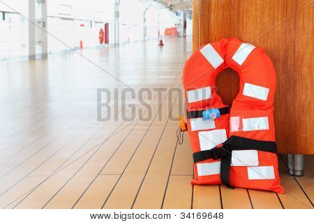 Singular orange life jacket stands on deck of cruise passenger liner