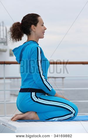 Young happy woman wearing in sports suit sits on cruise liner deck and looks into distance