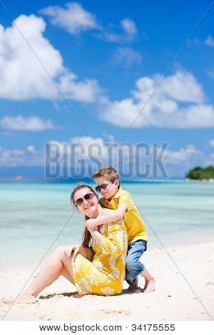Happy beautiful mother and son enjoying beach vacation