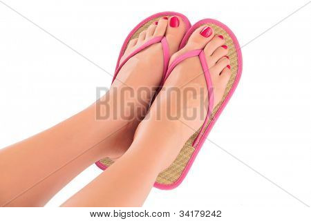 Female feet with pink flip-flops, isolated on white background.