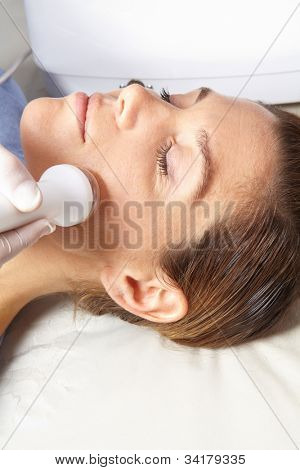Woman getting high frequency skin treatment in spa