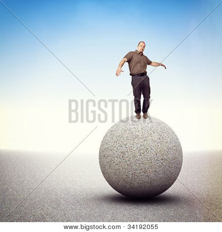 man try to balance himself isolated on big rock sphere