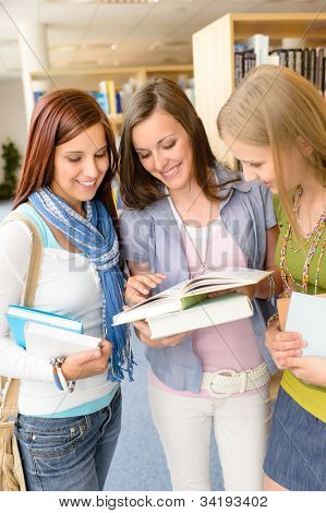Three female high school student standing with books at library