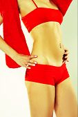 stock photo of partially clothed  - Woman In Red Active Wear Grabbing at Her Stomach - JPG