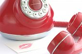 picture of long distance relationship  - a symbolic note rests by the phone with the receiver off the hook - JPG