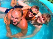 stock photo of family fun  - Summer Family Fun in beautiful small pool - JPG